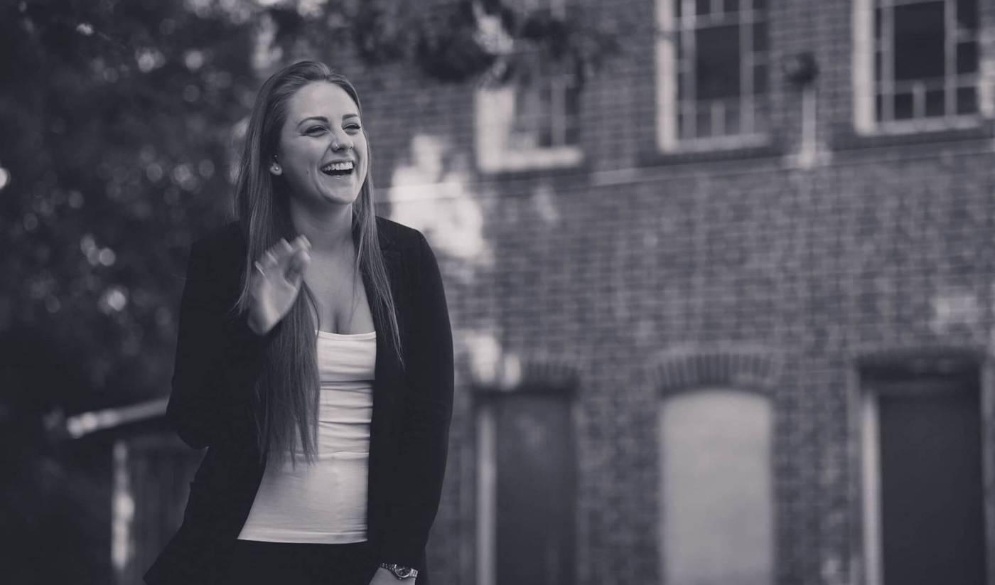 Sofia Orfei, Marketingberatung, im Hinterhof des Bürogebäudes. Sie lacht in die Kamera.