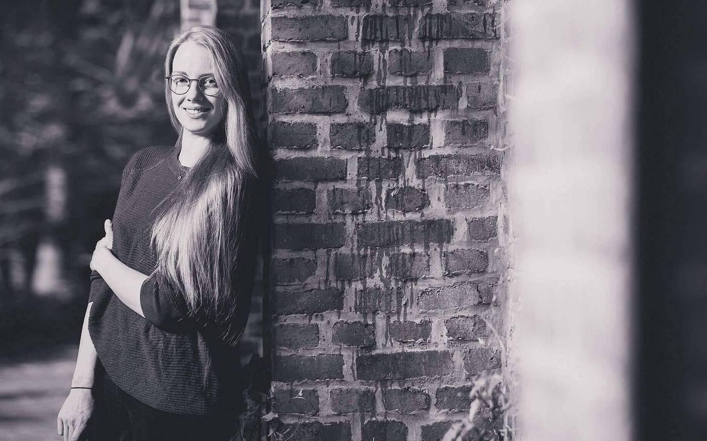 Laura Bremer, Konzept & Design, lehnt an der Mauer der Papierfabrik