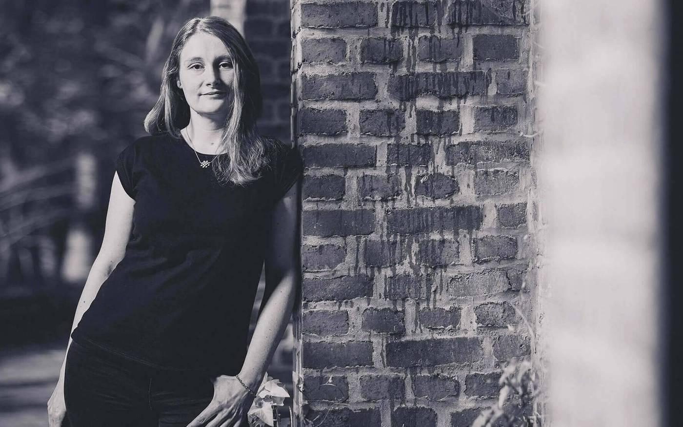 Melanie Vogel-Widner, Text & Social Media, lehnt am GEmäuer der Papierfabrik.