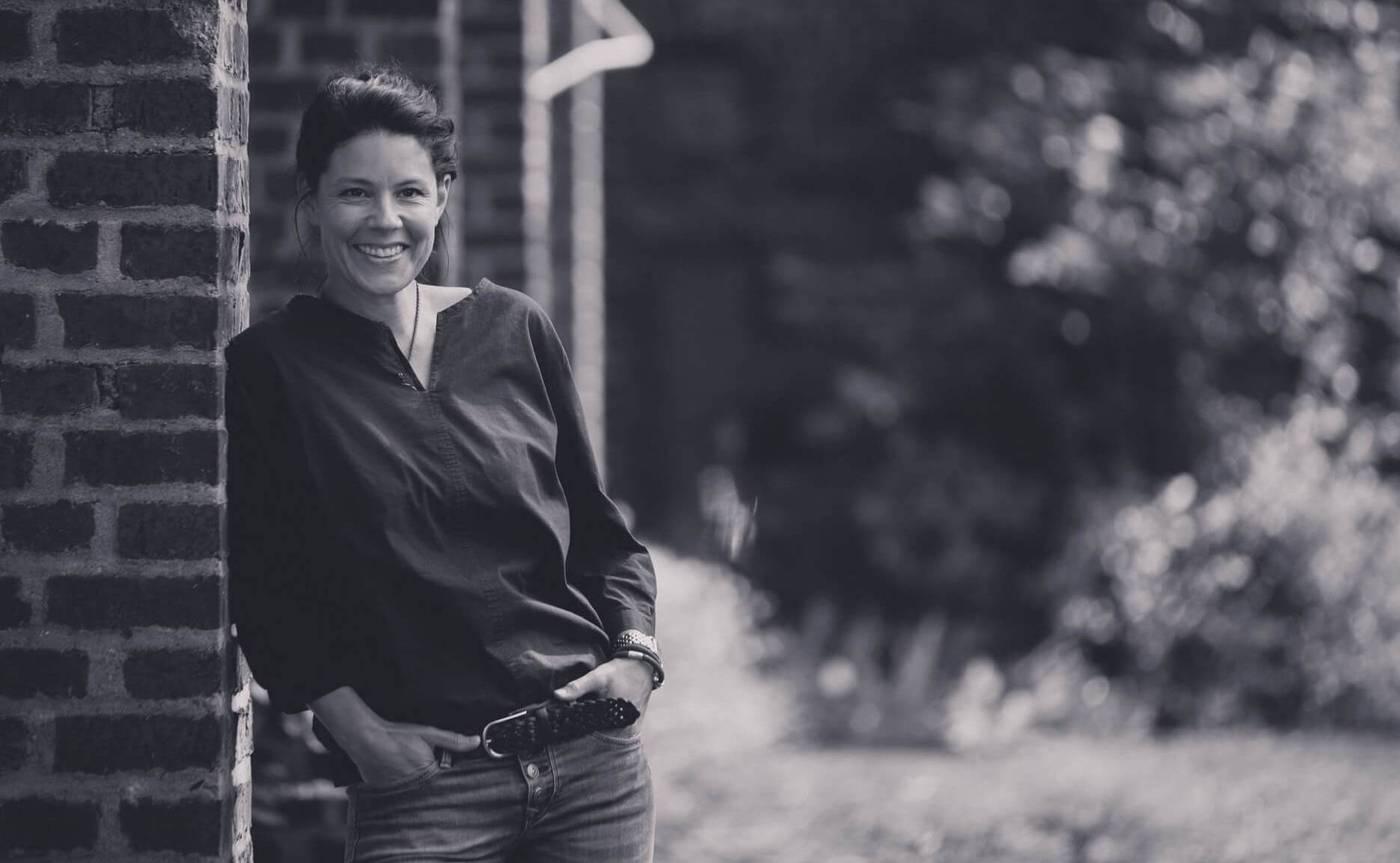 Jessica Boßlet, strategische Beratung, lehnt an Firmengebäude.